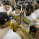 Michigan celebrates after a regional final game against Florida in the NCAA college basketball tournament, Sunday, March 31, 2013, in Arlington, Texas. Michigan won 79-59 to advance to the Final Four. (AP Photo/David J. Phillip)
