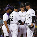 Colorado Rockies starting pitcher Jordan Lyles, far right, is pulled by manager Walt Weiss, second from left, as catcher Wilin Rosario, left, and shortstop Troy Tulowitzki look on after Lyles gave up a leadoff single to Philadelphia Phillies' Cody Asche i