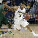 FILE - In this Nov. 13, 2012 file photo,Michigan guard Trey Burke (3) drives around Cleveland State guard Sebastian Douglas (1) during the first half of their NCAA college basketball game in the second-round of the NIT Season Tip-Off tournament at Crisler Arena in Ann Arbor, Mich. Burke was selected to the AP All-America team Monday, April 1, 2013. (AP Photo/Paul Sancya, File)