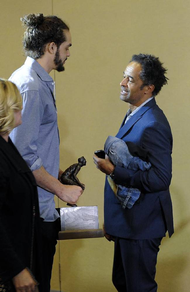Chicago Bulls center Joakim Noah, left, talks with his father, tennis star Yannick Noah, being named the NBA's Defensive Player of the Year, Monday, April 21, 2014, in Lincolnshire, Ill