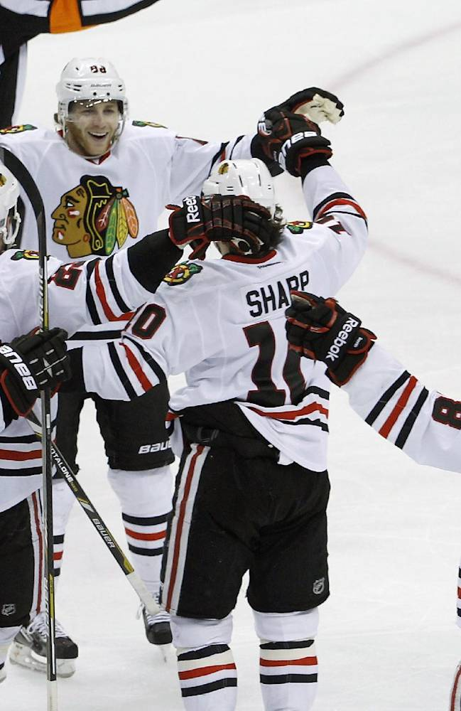 Teamamtes swarm Chicago Blackhawks right wing Patrick Kane, center, to celebrate his game-winning goal off Minnesota Wild goalie Ilya Bryzgalov to beat the Wild 2-1 during overtime of Game 6 of an NHL hockey second-round playoff series in St. Paul, Minn., Tuesday, May 13, 2014