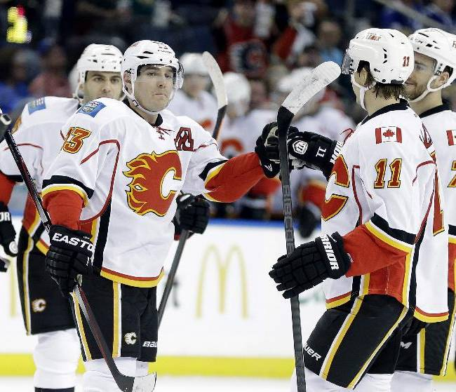 Calgary Flames left wing Mike Cammalleri (13) celebrates with teammates, including Mikael Backlund (11), of Sweden, and T.J. Brodie (7), after scoring against the Tampa Bay Lightning during the first period of an NHL hockey game on Thursday, April 3, 2014, in Tampa, Fla