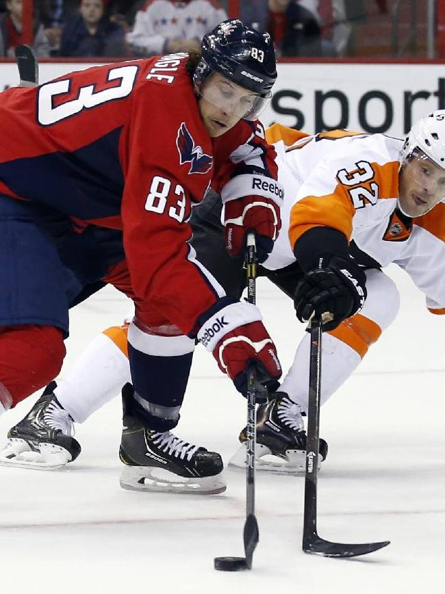 Washington Capitals center Jay Beagle (83) works the puck as he is defended by Philadelphia Flyers defenseman Mark Streit (32), from Switzerland, in the first period of an NHL hockey game, Sunday, Dec. 15, 2013, in Washington