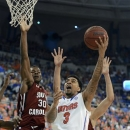 Florida guard Mike Rosario (3) goes to the basket to score against South Carolina's forward Lakeem Jackson (30) during the first half of an NCAA college basketball game in Gainesville, Fla., Wednesday, Jan. 30, 2013. (AP Photo/Phil Sandlin)