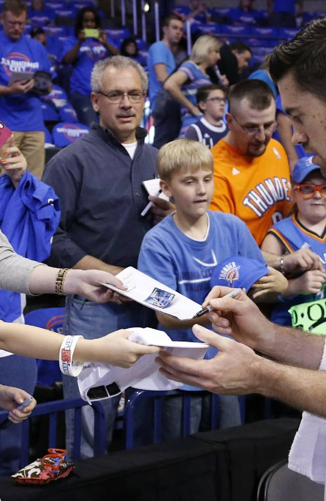 Oklahoma City Thunder forward Nick Collison, right, signs autographs for fans before the start of Game 1 of the Western Conference semifinal NBA basketball playoff series in Oklahoma City, Monday, May 5, 2014