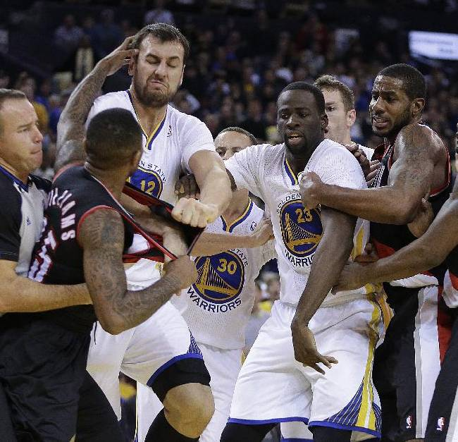 Portland Trail Blazers' Mo Williams, left, is restrained by a referee as he fights with Golden State Warriors' Andrew Bogut (12) during the second half of an NBA basketball game Saturday, Nov. 23, 2013, in Oakland, Calif. Trail Blazers Wesley Matthews (2), right, Mo Williams (25), and Warriors' Draymond Green (23) were ejected from the game
