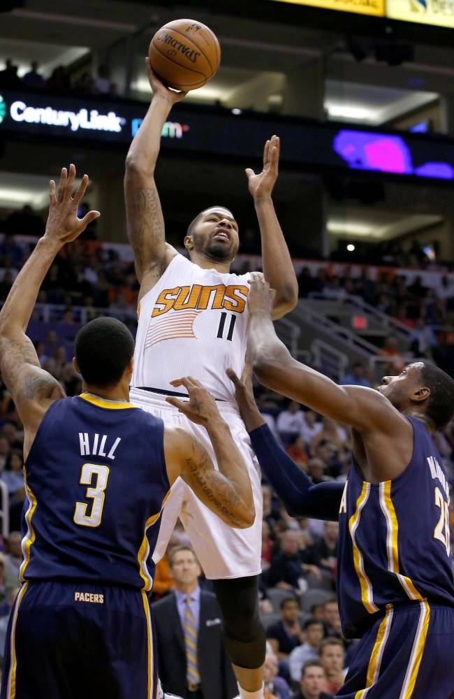 Phoenix Suns' Markieff Morris (11) gets off a shot and scores over Indiana Pacers' George Hill (3) and Ian Mahinmi, right, during the second half of an NBA basketball game Wednesday, Jan. 22, 2014, in Phoenix.  The Suns defeated the Pacers 124-100