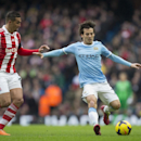 Manchester City's David Silva, right, keeps the ball from Stoke's Geoff Cameron during their English Premier League soccer match at the Etihad Stadium, Manchester, England, Saturday Feb. 22, 2014