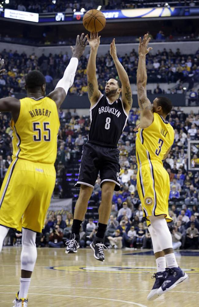 Brooklyn Nets guard Deron Williams (8) shoots between Indiana Pacers center Roy Hibbert, left, and guard George Hill in the first half of an NBA basketball game in Indianapolis, Saturday, Feb. 1, 2014