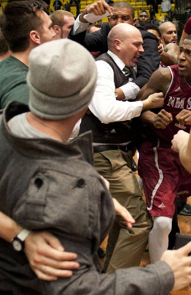 In this Thursday, Feb. 27, 2014 photo, New Mexico State's DK Eldridge, at right center in red and white uniform,  is controlled by security during a brawl involving players and fans who came onto the court when New Mexico State guard K.C. Ross-Miller hurled the ball at Utah Valley's Holton Hunsaker seconds after the Wolverines' 66-61 overtime victory against the Aggies in Orem, Utah