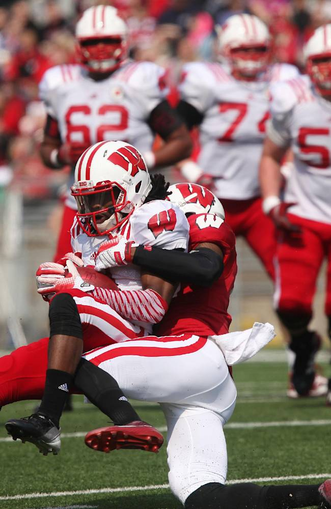 Wisconsin senior Kenzel Doe gets taken down by teammate junior Darius Hillary in the first half of a spring game at Camp Randall Stadium in Madison, Wis., Saturday, April 12, 2014