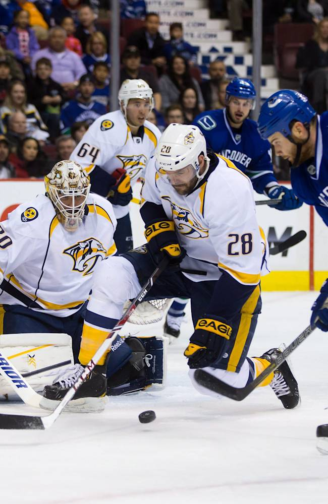 Vancouver Canucks' Zack Kassian, right, attempts a shot against Nashville Predators goalie Carter Hutton, left, as Paul Gaustad, center, defends and Victor Bartley (64) and Seth Jones (3) watch during first-period NHL hockey game action in Vancouver, British Columbia, Wednesday, March 19, 2014