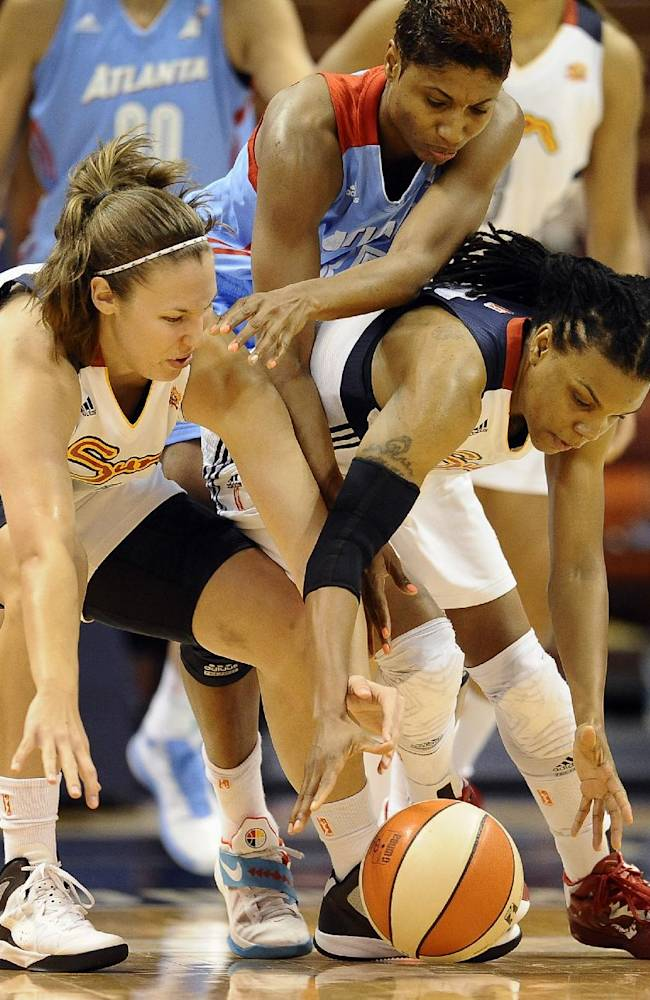 Connecticut Sun's Kayla Pedersen, left, and Tan White, right, chase a loose ball as Atlanta Dream's Angel McCoughtry, center, attempts to intercept during the second half of a WNBA basketball game in Uncasville, Conn., Wednesday, Sept. 11, 2013. Connecticut won 78-77