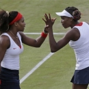 File - In this Monday, July 30, 2012 file photo, Serena Williams, left, and Venus Williams of the United States clasp hands as they compete against Sorana Cirstea and Simona Halep of Romania in women's doubles at the All England Lawn Tennis Club in Wimbledon, London, at the 2012 Summer Olympics. Serena and Venus Williams are teaming up at the French Open for the first time in three years. The sisters received a doubles wild card from the tournament on Saturday, May 25 2013,  allowing them to play in that event after skipping it in 2011 and 2012. (AP Photo/Elise Amendola, file)