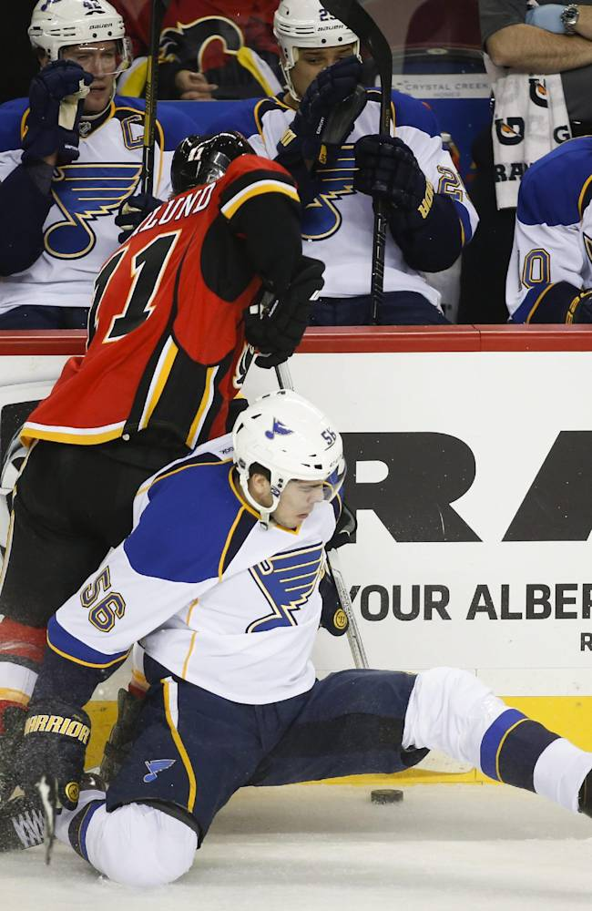 St. Louis Blues' Magnus Paajarvi, bottom, from Sweden, checks Calgary Flames' Mikael Backlund, top, also from Sweden, during first-period NHL hockey game action in Calgary, Alberta, Monday, Dec. 23, 2013