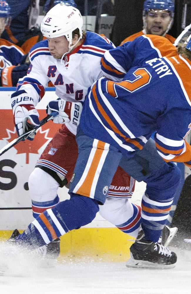 New York Rangers Derek Dorsett (15) is checked by Edmonton Oilers Jeff Petry (2) during first period NHL hockey action in Edmonton, Alberta., on Sunday March 30, 2014