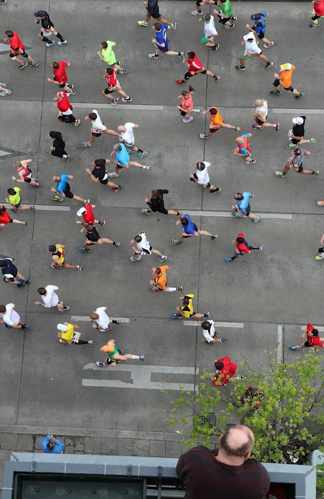 Athletes run past a balcony shortly after the start of the Vienna city marathon, in Vienna, Austria, on Sunday, April 13, 2014