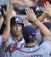 Atlanta Braves' Andrelton Simmons celebrates with teammates in the dugout after hitting a two-run home run during the third inning of a baseball game against the Chicago White Sox in Chicago, Friday, July 19, 2013. (AP Photo/Paul Beaty)