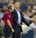 Sporting Kansas City coach Peter Vermes, right, talks with a game official during the first half of the championship US Open Cup soccer match with the Seattle Sounders FC in Kansas City, Kan., Wednesday, Aug. 8, 2012. (AP Photo/Orlin Wagner)