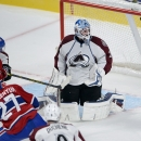 Montreal Canadiens center Alex Galchenyuk (27) scores the winning goal in overtime on Colorado Avalanche goalie Reto Berra (20) during an NHL hockey preseason game Thursday, Sept. 25, 2014, in Montreal. Montreal won 3-2. The Associated Press