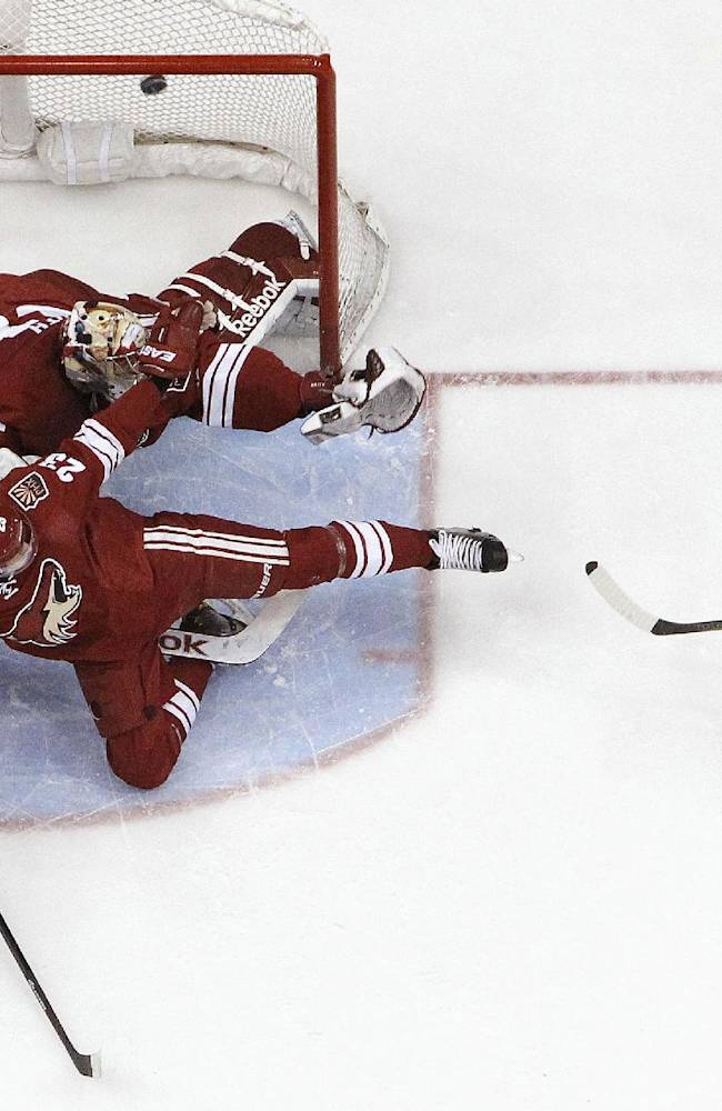 Vancouver Canucks' Daniel Sedin, right, of Sweden, shoots the puck over the goal as Phoenix Coyotes' Mike Smith, top left, and teammate Oliver Ekman-Larsson (23), of Sweden, both dive to cover the open net, as Canucks' Ryan Kesler (17) and Coyotes' Lauri Korpikoski, bottom left, of Finland, collide during the second period of an NHL hockey game Thursday, Jan. 16, 2014, in Glendale, Ariz.  The Coyotes defeated the Canucks 1-0