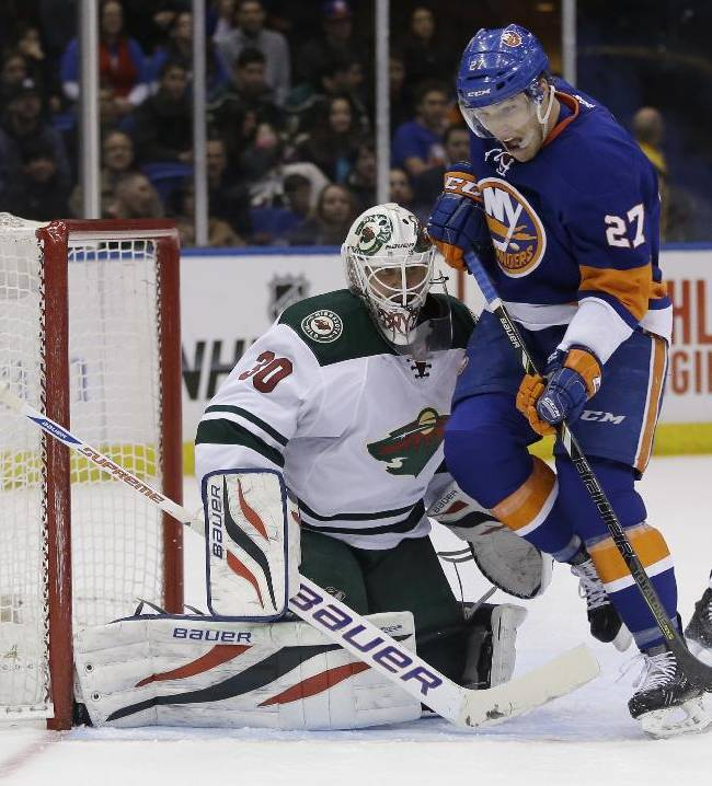 Minnesota Wild goalie Ilya Bryzgalov, left defends the goal while New York Islanders' Anders Lee skates past during the second period of the NHL hockey game, Tuesday, March 18, 2014, in Uniondale, New York