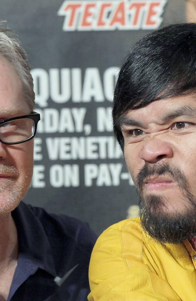 Manny Pacquiao, right, of the Philippines, and his trainer Freddie Roach, left, appear at a news conference in Beverly Hills, Calif., Thursday, Aug 8, 2013, to promote Pacquiao's upcoming boxing match against Brandon Rios. Pacquiao and Rios are scheduled to fight in a welteweight match at The Venetian Macao in Macau on Nov. 24
