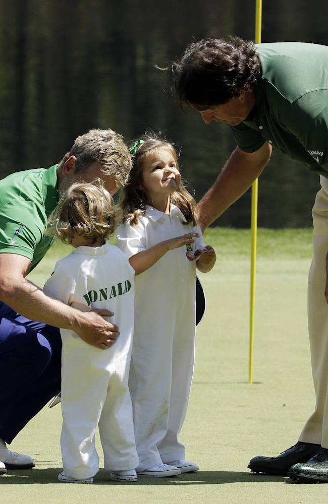 Phil Mickelson, right, talks to Luke Donald, of England's daughters Sophie and Elle during the par three competition at the Masters golf tournament Wednesday, April 9, 2014, in Augusta, Ga