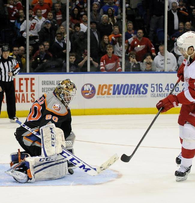 New York Islanders goalie Kevin Poulin (60) blocks a shot on goal by Detroit Red Wings' Pavel Datsyuk (13) during a shootout of an NHL hockey game on Saturday, Nov. 16, 2013, in Uniondale, N.Y. The Islanders won 5-4 on Frans Nielsen's shootout goal against Detroit Red Wings goalie Jonas Gustavsson