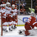 Carolina Hurricanes' Andrei Loktionov, left, of Russia; Elias Lindholm, center, of Sweden; and Riley Nash celebrate Lindholm's goal behind Detroit Red Wings goalie Jimmy Howard during the first period of an NHL hockey game in Detroit, Friday, April 11, 20