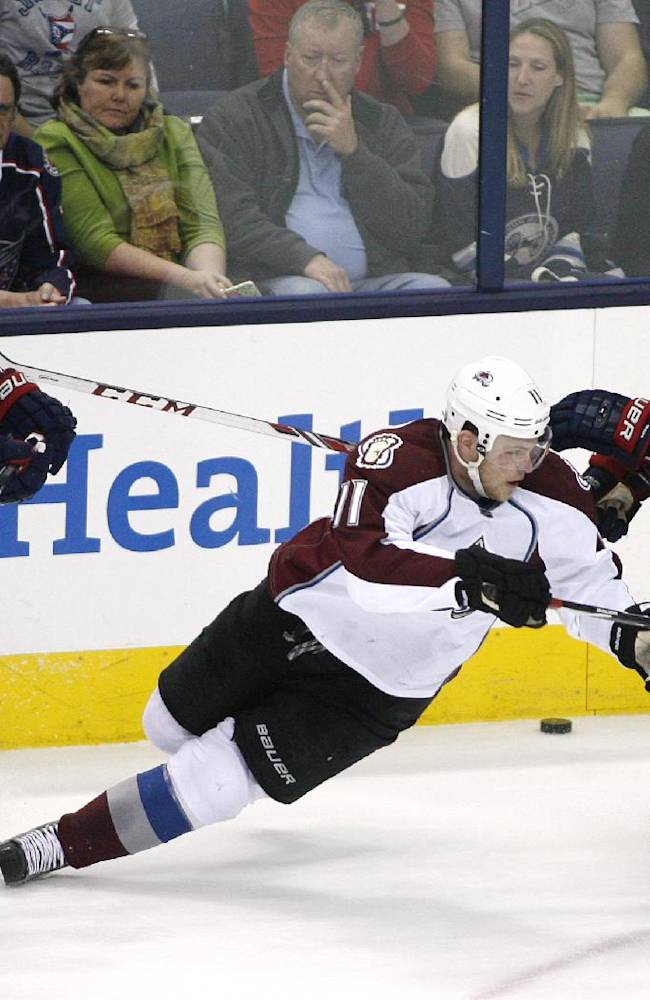 Colorado Avalanche's Jamie McGinn (11) loses his footing between Columbus Blue Jackets' Ryan Johansen (19) and Boone Jenner (38) during the third period of an NHL hockey game, Tuesday, April 1, 2014, in Columbus, Ohio