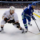 Vancouver Canucks' Zack Kassian, right, moves the puck along the boards as Anaheim Ducks' Saku Koivu, of Finland, defends during the first period of an NHL hockey game Saturday, March 29, 2014, in Vancouver, British Columbia The Associated Press