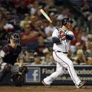 Atlanta Braves' Brian McCann (16) follows through with a solo home run as Minnesota Twins catcher Joe Mauer (7) watches in the fourth inning of a baseball game Tuesday, May 21, 2013 in Atlanta. (AP Photo/John Bazemore)