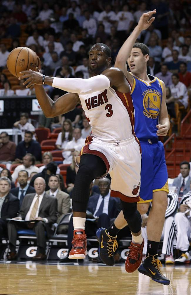 Miami Heat's Dwyane Wade (3) passes as Golden State Warriors' Klay Thompson (11) defends during the first half of an NBA basketball game, Thursday, Jan. 2, 2014, in Miami