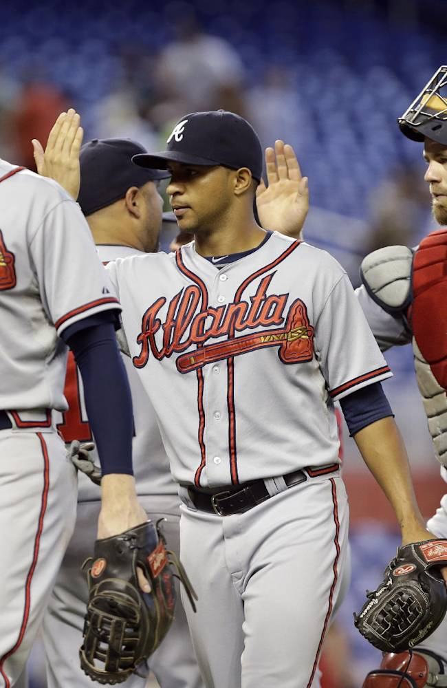 Atlanta Braves first baseman Freddie Freeman, left, relief pitcher Anthony Varvaro, center, and catcher Evan Gattis, right, high-five their teammates after defeating the Miami Marlins 6-1 in a baseball game, Thursday, Sept. 12, 2013, in Miami