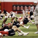 Nebraska head coach Bo Pelini, right, chats with his quarterbacks during warmups on the first day of spring NCAA college football practice in Lincoln, Neb., Saturday, March 2, 2013. (AP Photo/Nati Harnik)