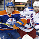 New York Rangers' Rick Nash (61) and Edmonton Oilers' David Perron (57) battle for the puck during first period NHL hockey action in Edmonton, Alberta, on Sunday, Dec. 14, 2014 The Associated Press