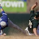 Los Angeles Dodgers shortstop Miguel Rojas, left, reaches with his foot towards second base as Oakland Athletics' Chris Gimenez, right, is caught stealing second during the seventh inning of a spring training baseball game Monday, March 3, 2014, in Phoen