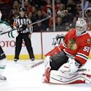 Dallas Stars center Cody Eakin, left, celebrates Valeri Nichushkin's goal as the puck bounces back out of the net behind Chicago Blackhawks goalie Corey Crawford during the first period of an NHL hockey game Tuesday, Dec. 3, 2013, in Chicago. (AP Photo/Charles Rex Arbogast)