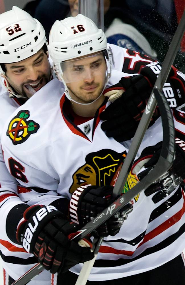 Chicago Blackhawks' Brandon Bollig, left, and Marcus Kruger, of Sweden, celebrate Kruger's goal against the Vancouver Canucks during third period NHL hockey action in Vancouver, British Columbia Saturday Nov. 23, 2013