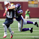 New England Patriots wide receiver Julian Edelman, left, runs with the ball for a gain before being brought down by Minnesota Vikings cornerback Xavier Rhodes, right, during the first quarter of an NFL football game Sunday, Sept. 14, 2014, in Minneapolis
