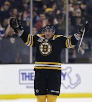 Boston Bruins left wing Brad Marchand raises his arms as he celebrates after his game-winning goal during overtime against the Nashville Predators in an NHL hockey game, Thursday, Jan. 2, 2014, in Boston. The Bruins won 3-2. (AP Photo/Charles Krupa)