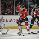 Chicago Blackhawks' Brad Richardson tries to control the puck in front of Detroit Red Wings goalie Jonas Gustavsson in an NHL exhibition hockey game in Chicago on Tuesday, Sept. 23, 2014. The Associated Press