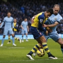 Manchester City's Pablo Zabaleta, right challenges Arsenal's Alexis Sanchez for the ball during the English Premier League soccer match between Manchester City and Arsenal at the Etihad Stadium, Manchester, England, Sunday Jan. 18, 2015