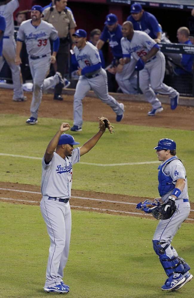 Los Angeles Dodgers' Kenley Jansen, left, and A.J. Ellis, right, celebrate their win to capture the Western Division National League Championship after a baseball game against the Arizona Diamondbacks, Thursday, Sept. 19, 2013, in Phoenix. The Dodgers won 7-6