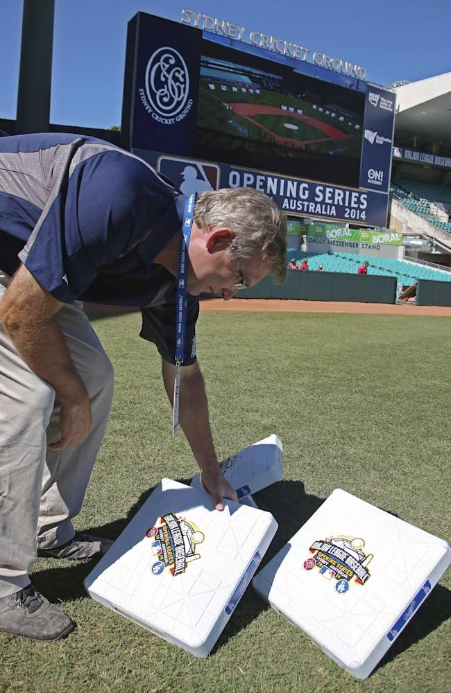 Murray Cook, the MLB field and stadium consultant, places on the field bases with commemorative logos on them as preparations are made for the Major League Baseball opening game between the Los Angeles Dodgers and the Arizona Diamondbacks at the Sydney Cricket ground in Sydney, Saturday, March 22, 2014