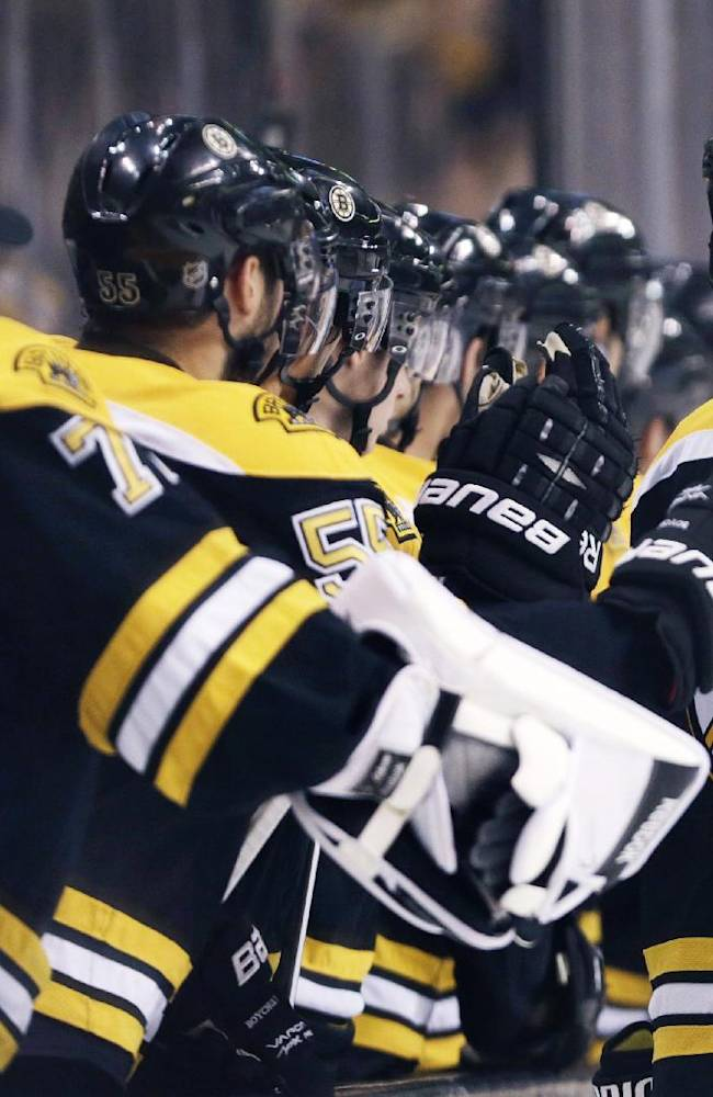Boston Bruins defenseman Zdeno Chara, of Slovakia, is congratulated by teammates after a goal against the Washington Capitals during the third period of an NHL preseason hockey game, Monday, Sept. 23, 2013, in Boston. Chara scored twice in the Bruins' 3-2 overtime win