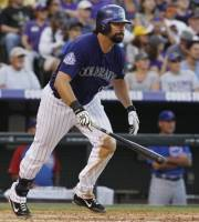 Colorado Rockies' Todd Helton follows the flight of his single against the Chicago Cubs in the fourth inning of a baseball game in Denver on Saturday, July 20, 2013, in Denver. (AP Photo/David Zalubowski)