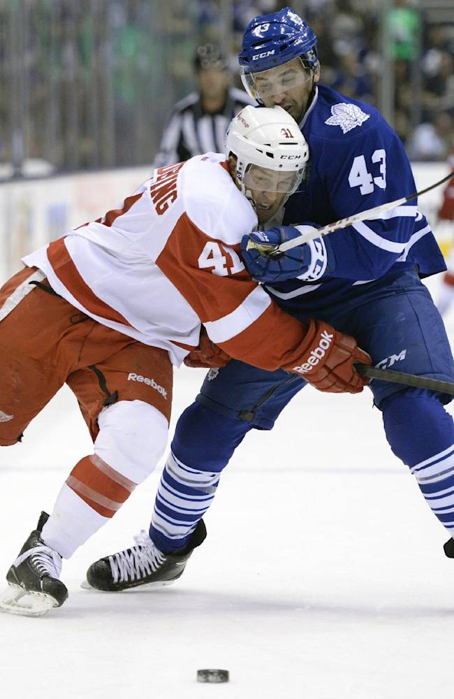 Toronto Maple Leafs' Nazem Kadri, right, takes a penalty for holding on Detroit Red Wings' Luke Glendening during first-period preseason NHL hockey game action in Toronto, Saturday Sept. 28, 2013