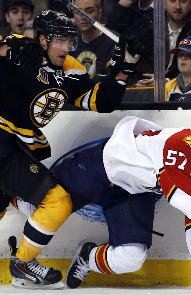 Florida Panthers center Marcel Goc (57) goes down along the boards as he chases the puck against Boston Bruins defenseman Johnny Boychuk (55) during the first period of an NHL hockey game in Boston, Tuesday, March 4, 2014